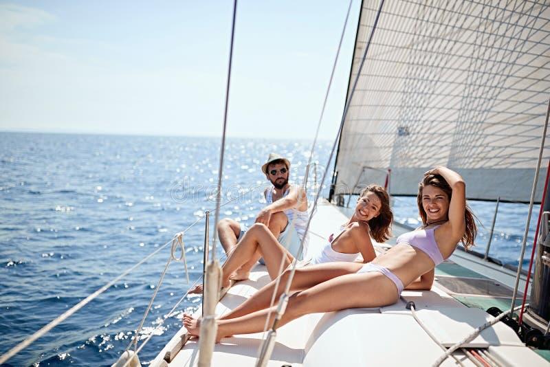 Amigos novos que sentam-se na plataforma do iate Navegando o mar imagens de stock royalty free