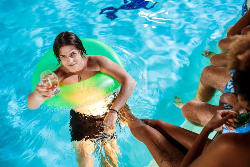 Amigos novos que sorriem, exultando, descansando no partido perto da piscina fotografia de stock royalty free