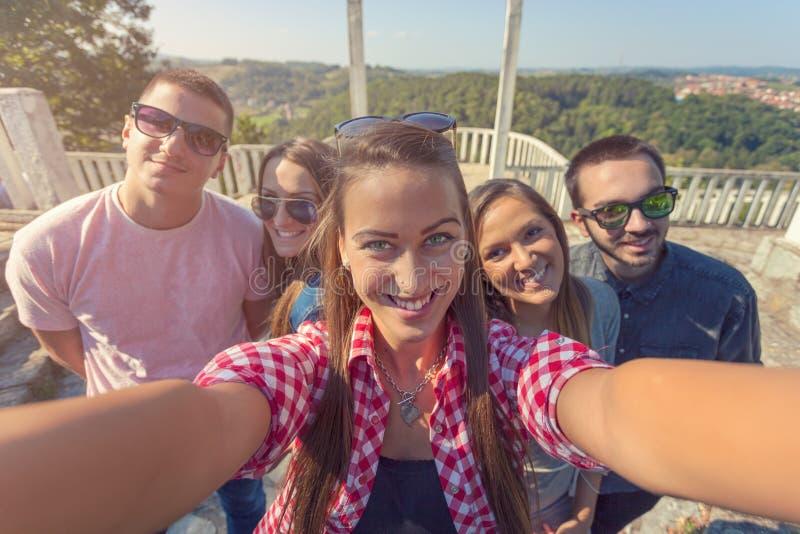 Amigos novos que têm o divertimento e que tomam o selfie fora fotos de stock royalty free
