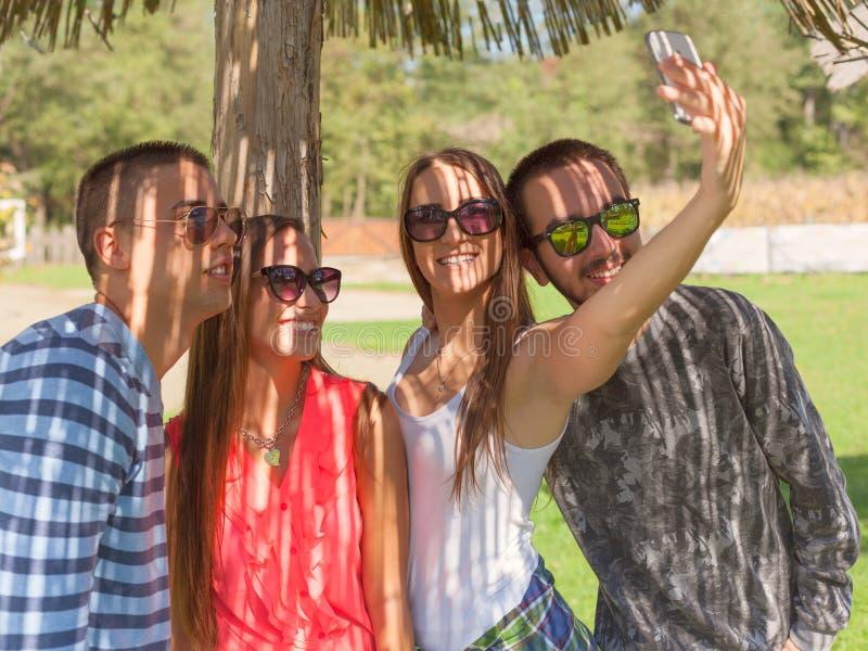 Amigos novos que têm o divertimento e que tomam o selfie fora imagem de stock