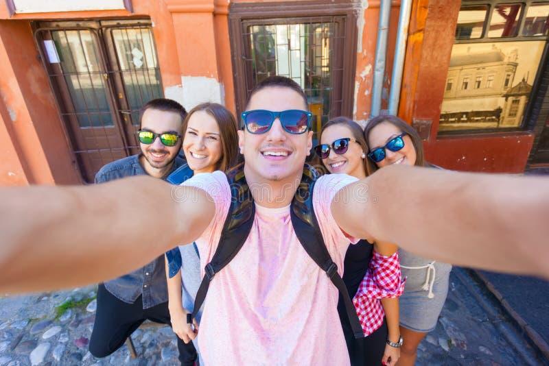 Amigos novos que têm o divertimento e que tomam o selfie fora foto de stock