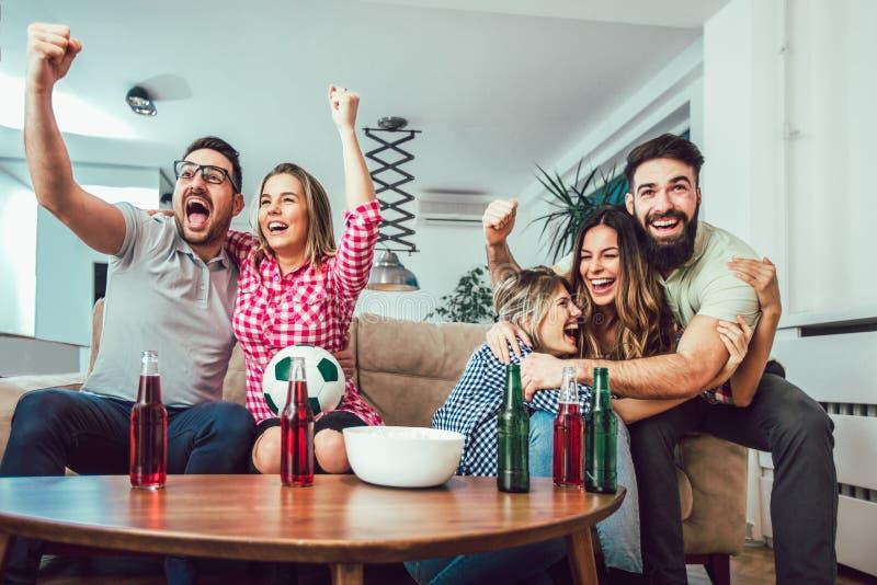 Amigos o fanáticos del fútbol felices que miran fútbol en la TV imagenes de archivo