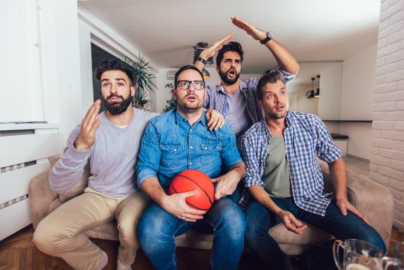 Amigos o fans de baloncesto que miran el juego de baloncesto en la TV y que celebran la victoria en casa Amistad, deportes y foto de archivo