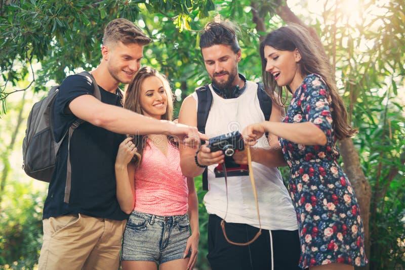Amigos o pares que se divierten con la cámara de la foto en parque fotografía de archivo libre de regalías