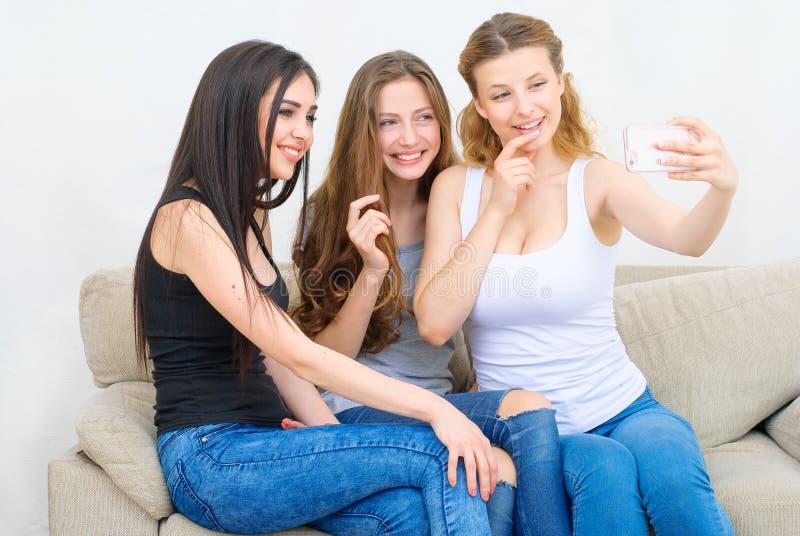 Amigos ou adolescentes felizes com o smartphone que toma o selfie fotografia de stock