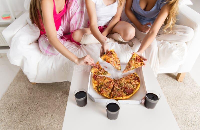Amigos ou meninas adolescentes que comem a pizza em casa fotografia de stock