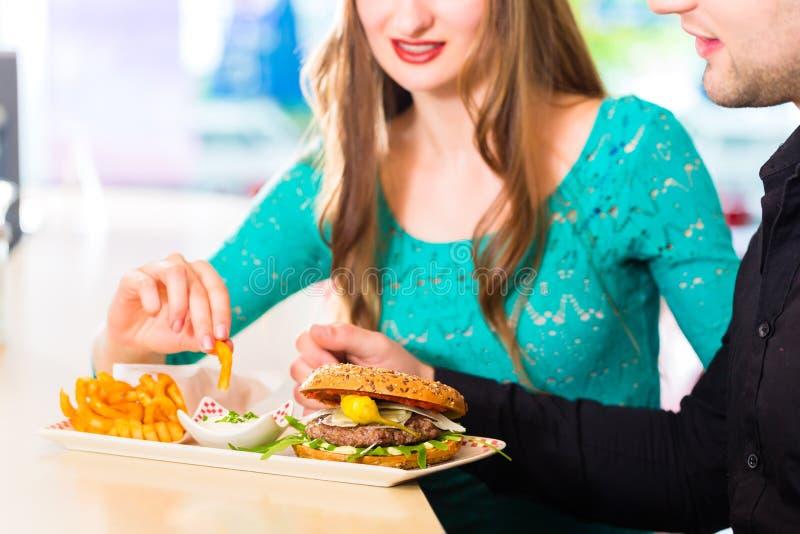 Amigos ou pares que comem o fast food com hamburguer e fritadas imagens de stock