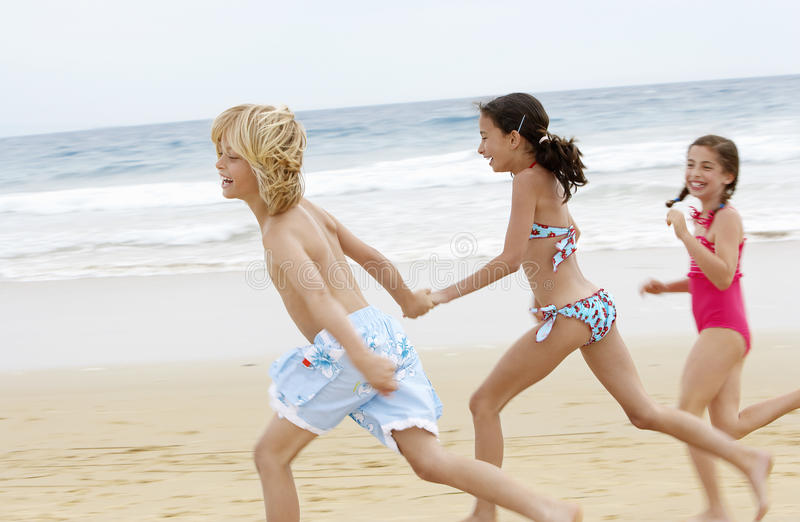 Amigos pequenos alegres que correm junto na praia foto de stock