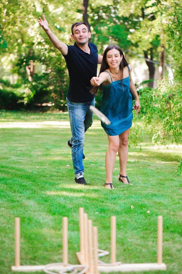 Amigos plaing los juegos al aire libre - lanzamiento del anillo El individuo y la muchacha compiten en el lanzamiento del anillo imagen de archivo