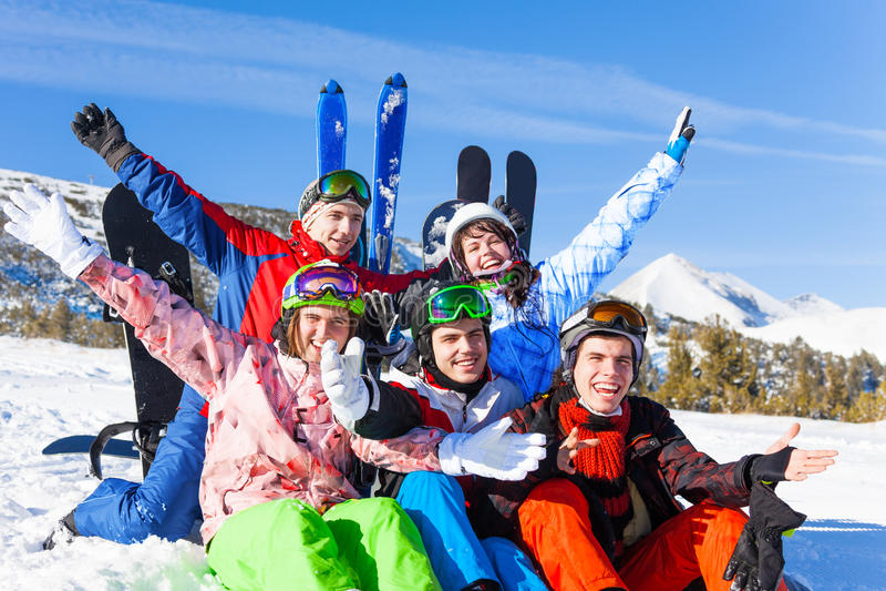 Amigos positivos com os snowboards que levantam as mãos acima fotografia de stock royalty free