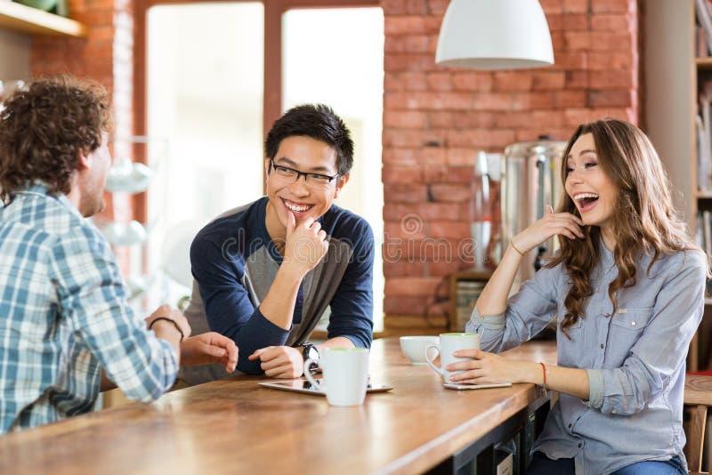 Amigos positivos felizes que riem no café imagens de stock