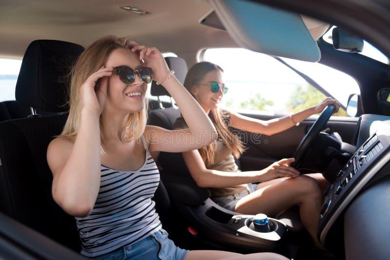 Amigos positivos que conducen un coche imágenes de archivo libres de regalías