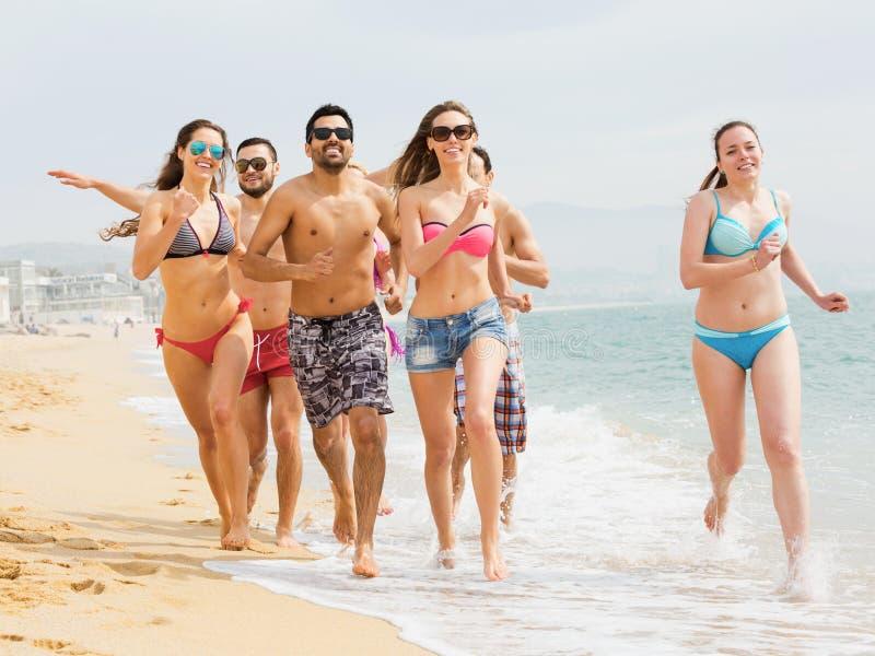 Amigos positivos que corren en traje de baño imagenes de archivo