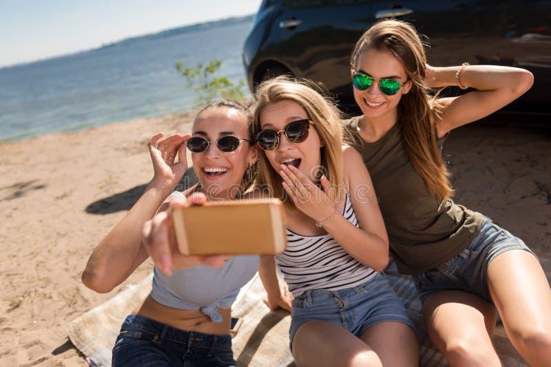 Amigos positivos que fazem selfies fotografia de stock