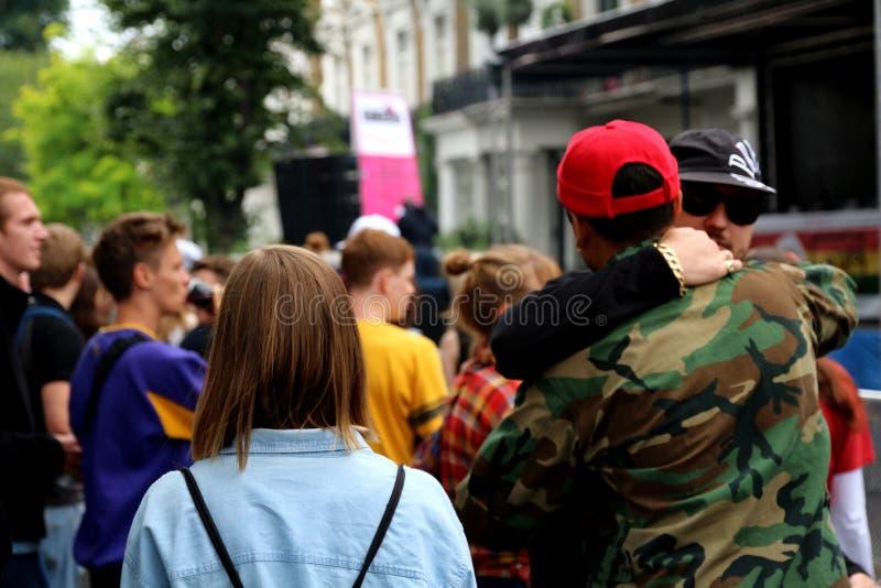 Amigos que abraçam na rua aglomerada imagem de stock royalty free