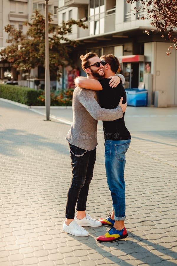 Amigos que abraçam na rua e no sorriso fotos de stock