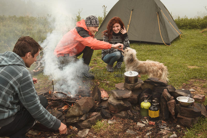 Amigos que acampan con el perro cerca de hoguera imagen de archivo