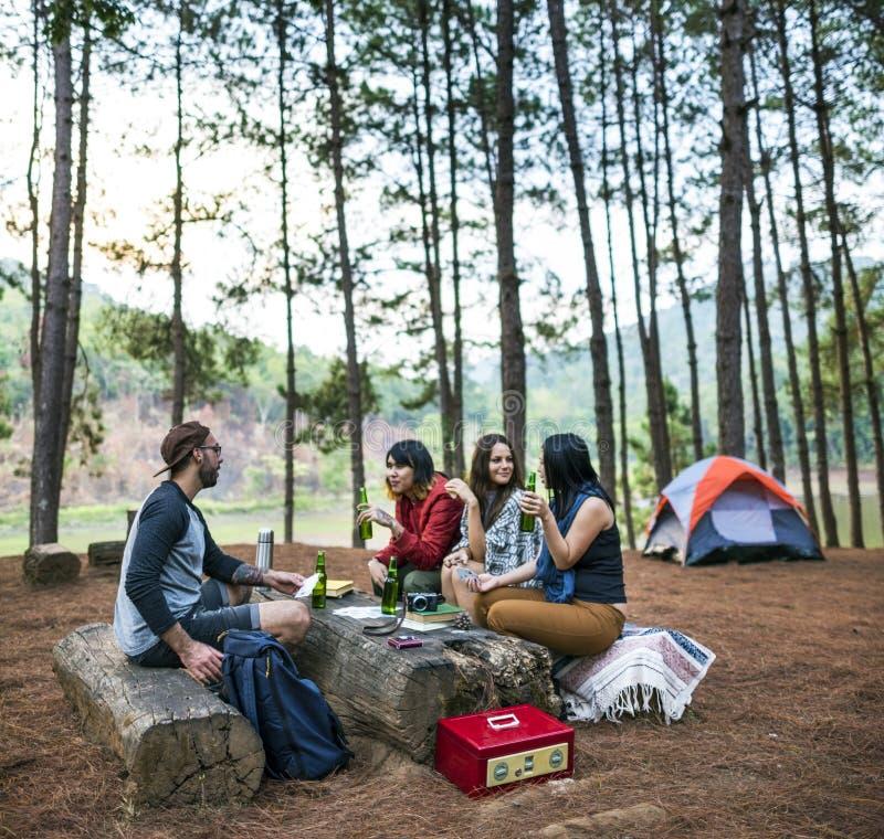 Amigos que acampan teniendo concepto de las bebidas fotografía de archivo