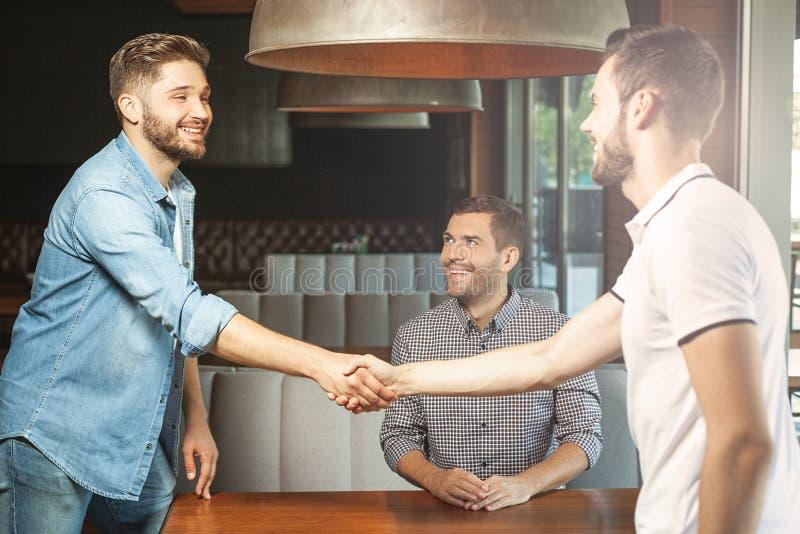Amigos que agitam as mãos no café fotografia de stock