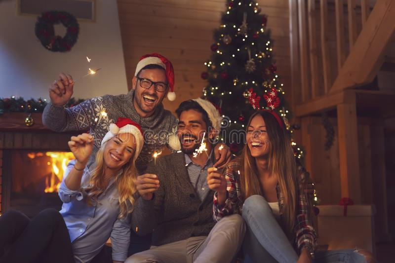 Amigos que agitan con las bengalas en cuenta descendiente de medianoche del Año Nuevo fotos de archivo libres de regalías
