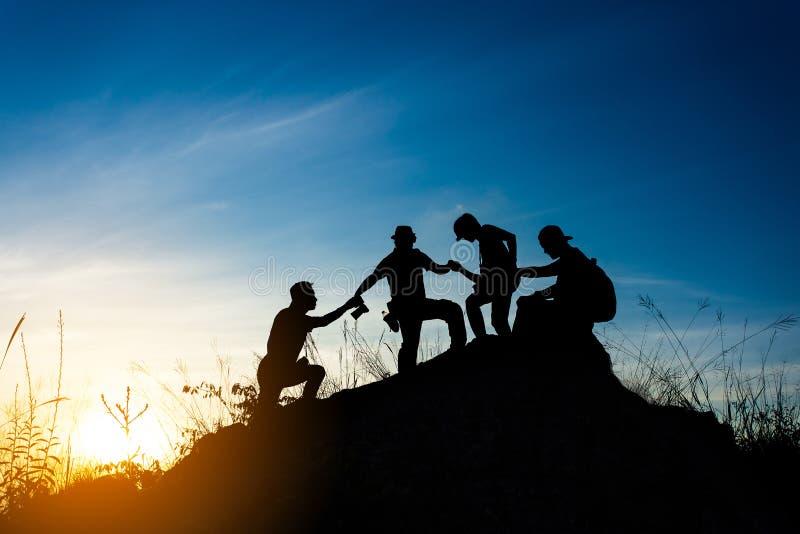 amigos que ajudam-se e com os trabalhos de equipe que tentam alcançar a parte superior das montanhas durante o por do sol maravil fotos de stock royalty free