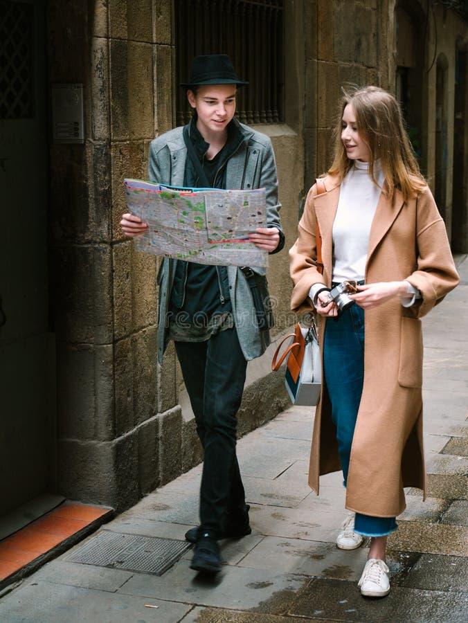 Amigos que andam junto através da rua apertada imagem de stock royalty free