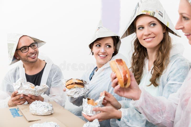 Amigos que apreciam o fast food na casa nova fotos de stock