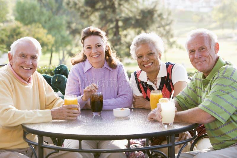 Amigos que apreciam uma bebida por um campo de golfe foto de stock royalty free