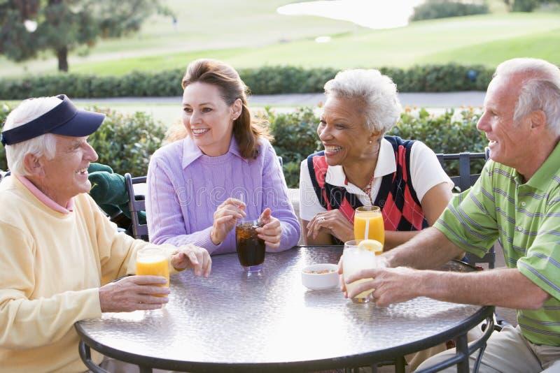Amigos que apreciam uma bebida por um campo de golfe imagem de stock