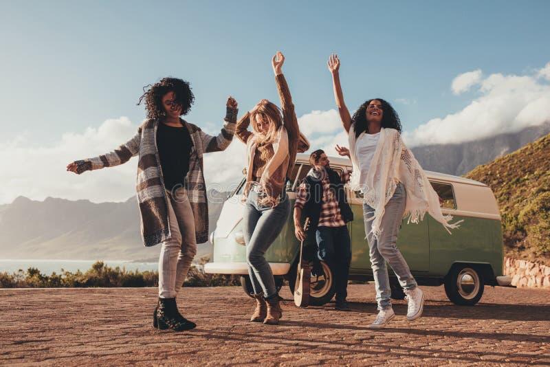Amigos que bailan al aire libre en roadtrip imagen de archivo