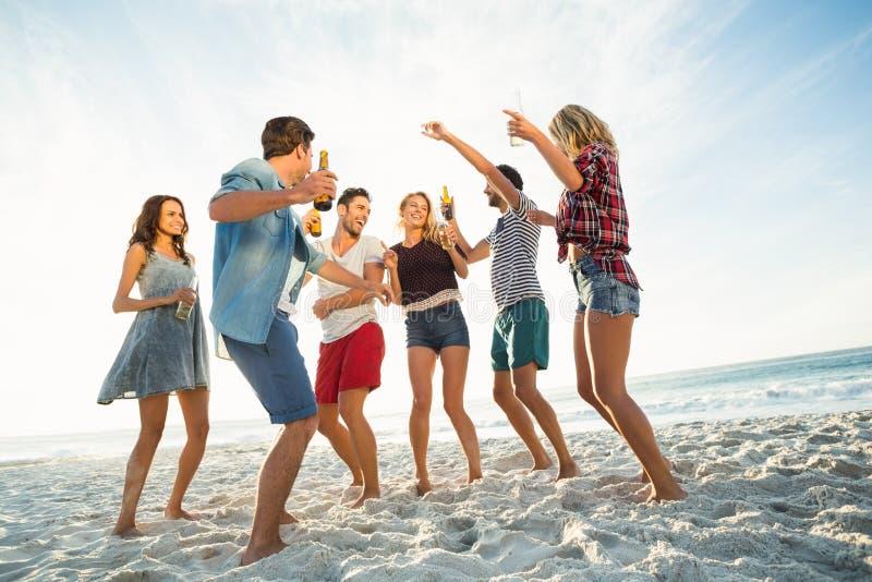 Amigos que bailan en la playa fotos de archivo
