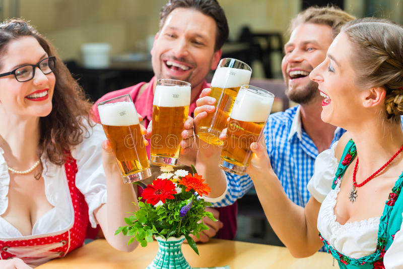 Amigos que bebem a cerveja no restaurante ou no bar bávaro foto de stock
