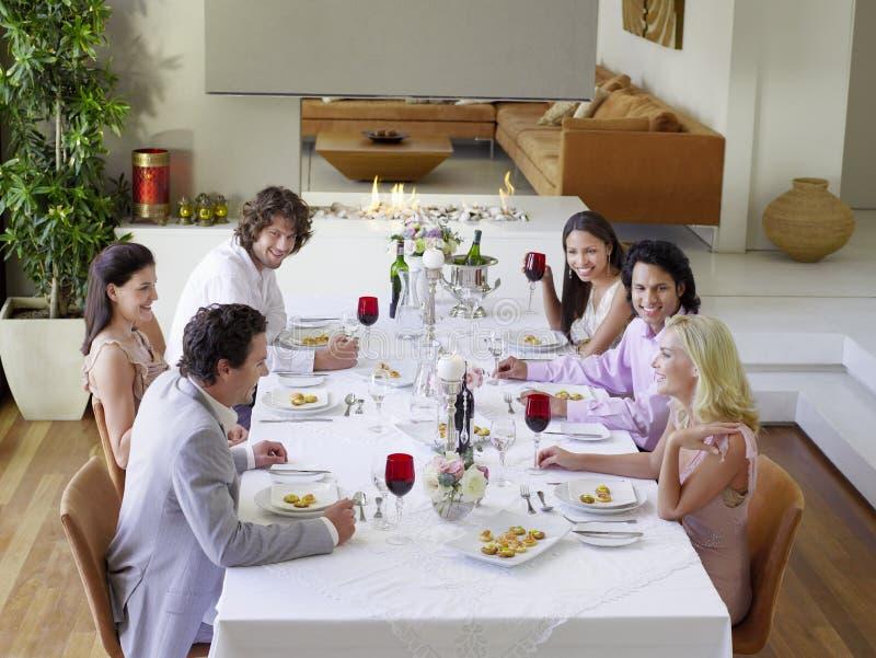 Amigos que bebem e que socializam no partido de jantar fotografia de stock