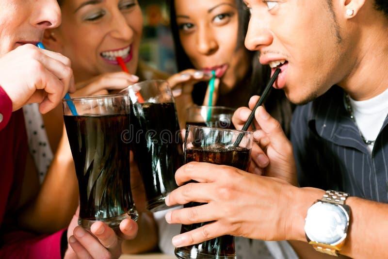 Amigos que beben soda en una barra foto de archivo