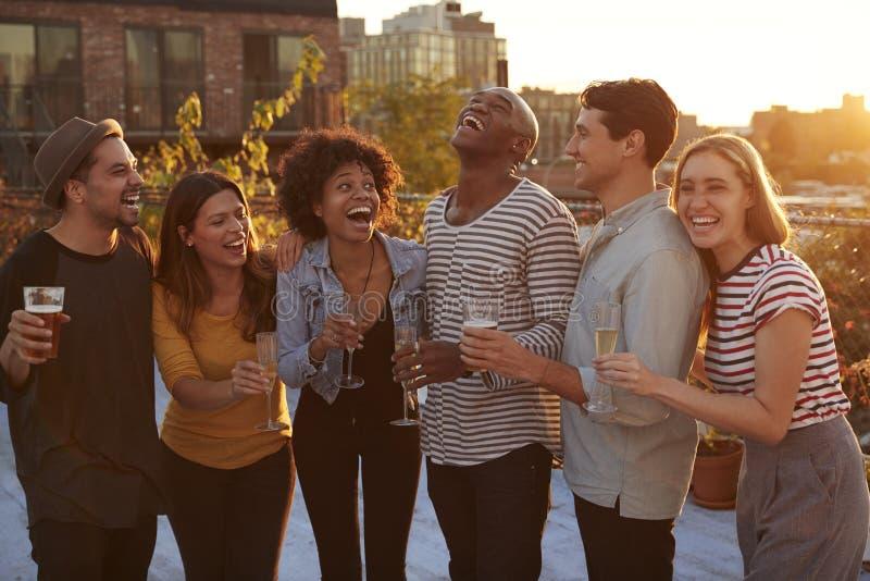 Amigos que beben y que se ríen de un partido del tejado en Brooklyn fotos de archivo libres de regalías