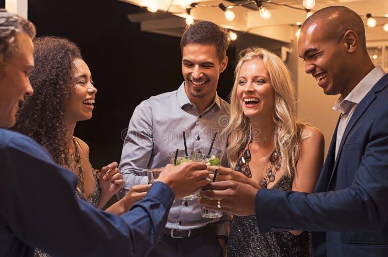 Amigos que brindam o cocktail no partido da noite imagem de stock