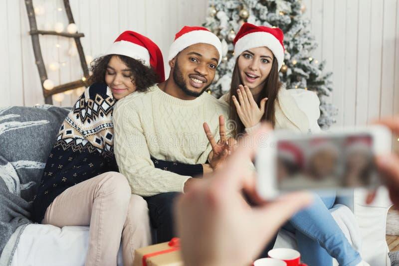 Amigos que capturan el momento precioso de la Navidad foto de archivo libre de regalías