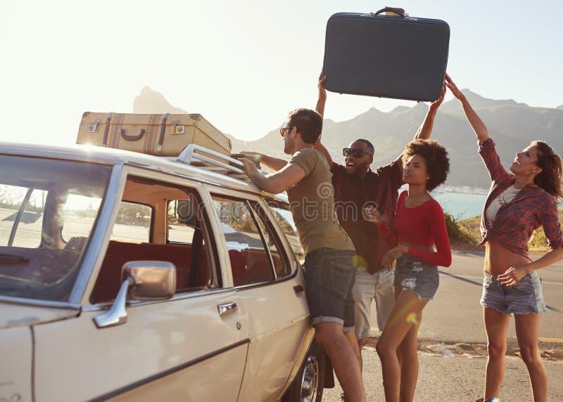 Amigos que carregam a bagagem na grade de tejadilho do carro pronta para a viagem por estrada fotografia de stock