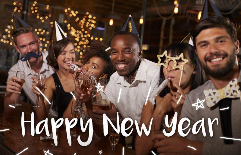 Amigos que celebran en un partido con el mensaje de la Feliz Año Nuevo fotografía de archivo libre de regalías