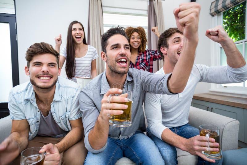 Amigos que cheering ao olhar o fósforo de futebol na tevê fotos de stock royalty free