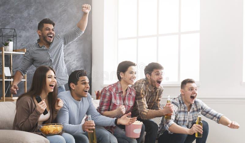 Amigos que cheering a equipe de futebol favorita, fósforo de observação em casa foto de stock royalty free