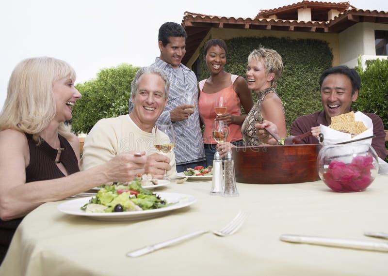 Amigos que comem e que bebem no jardim imagem de stock royalty free