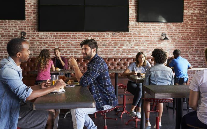 Amigos que comem para fora na barra de esportes com as telas no fundo foto de stock royalty free
