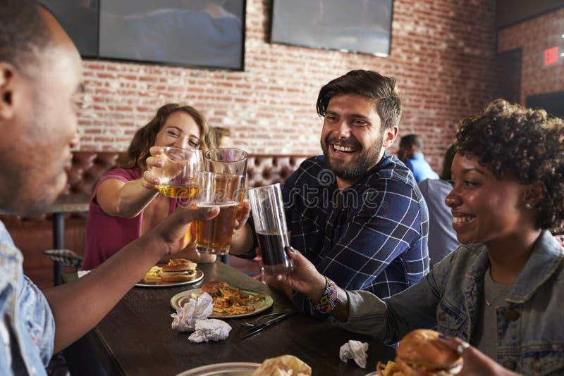 Amigos que comem para fora na barra de esportes com as telas no fundo imagens de stock