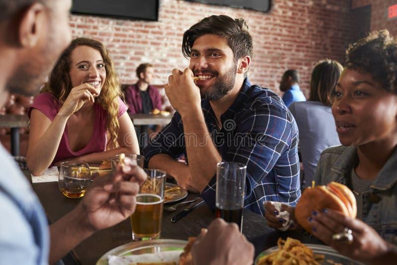 Amigos que comem para fora na barra de esportes com as telas no fundo imagens de stock royalty free