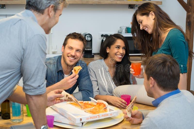 Amigos que comem a pizza imagens de stock royalty free