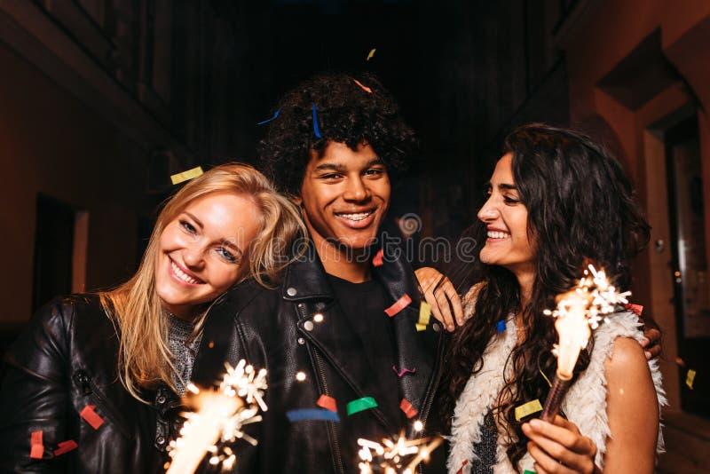 Amigos que comemoram com sparkles do fogo foto de stock