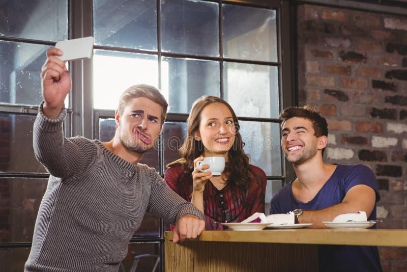 Amigos que comen café y que toman selfies divertidos imagenes de archivo