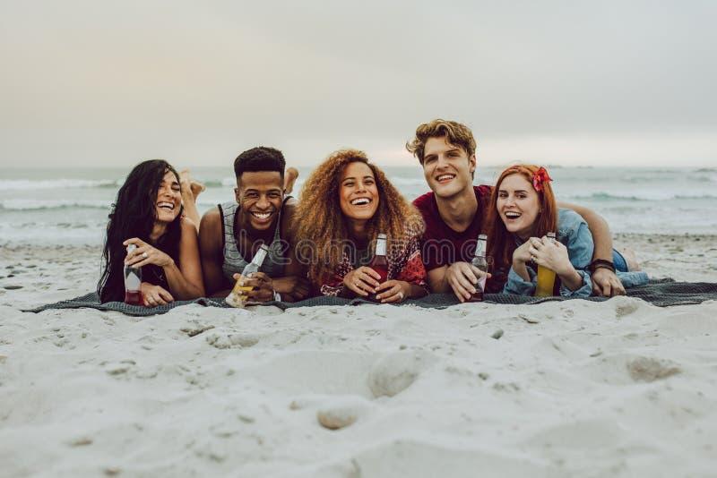 Amigos que comen cervezas en la orilla de mar fotografía de archivo