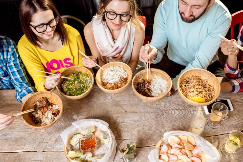 Amigos que comen comidas asiáticas fotografía de archivo
